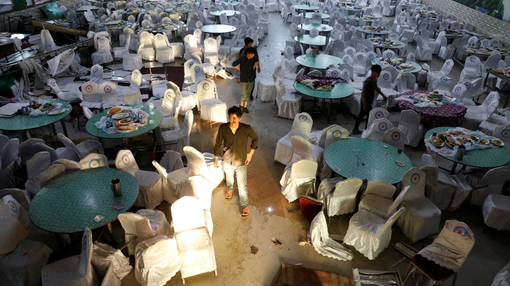 Workers inspect a damaged wedding hall after a blast in Kabul, Afghanistan
