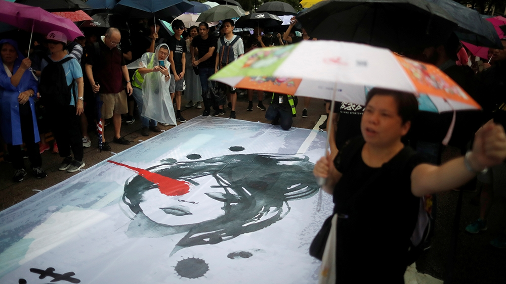 Anti-extradition bill protesters demonstrate next to a banner depicting a woman with an injured right eye during a rally to demand democracy and political reforms in Hong Kong, China, August 18, 2019.