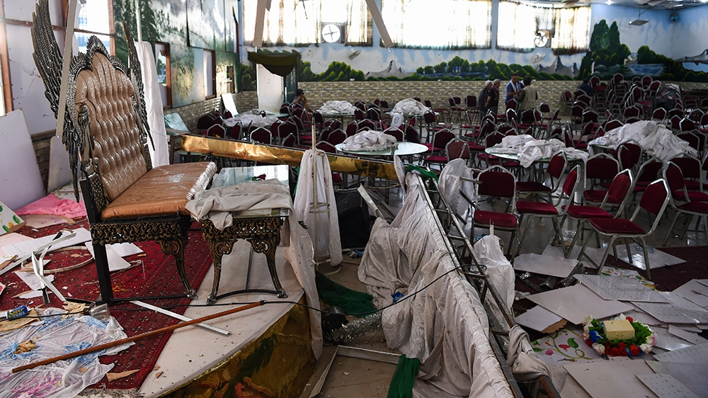Afghan men investigate in a wedding hall after a deadly bomb blast in Kabul on August 18, 2019. - More than 60 people were killed and scores wounded in an explosion targeting a wedding in the Afghan c