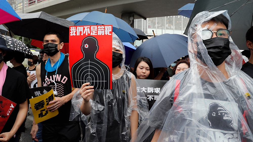 Protesters, some wearing eye patches to show solidarity to a woman reportedly injured in the eye by a beanbag fired by police, hold up a banner which reads