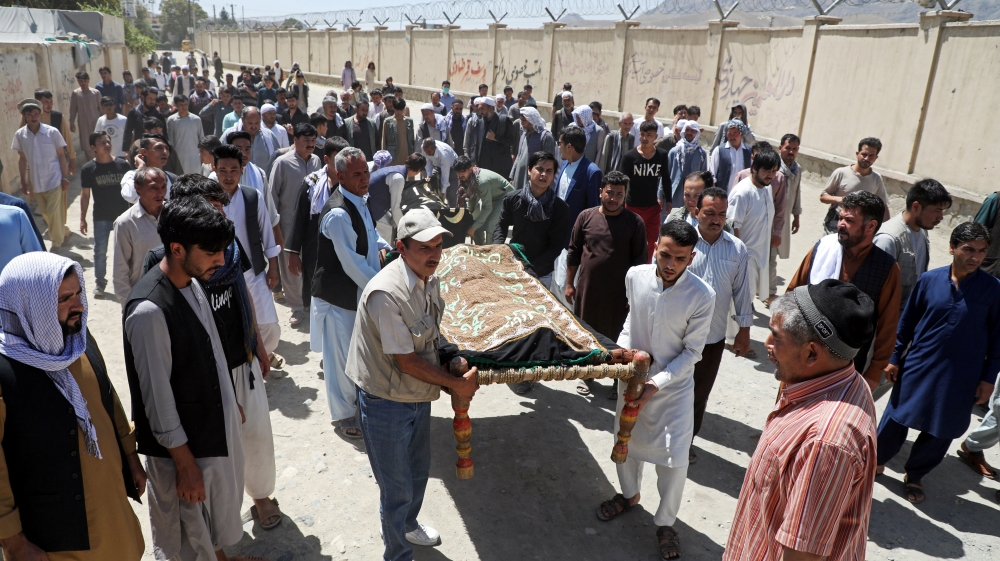 Afghan men carry the bodies of the victims during a mass funeral after a suicide bomb blast at a wedding in Kabul