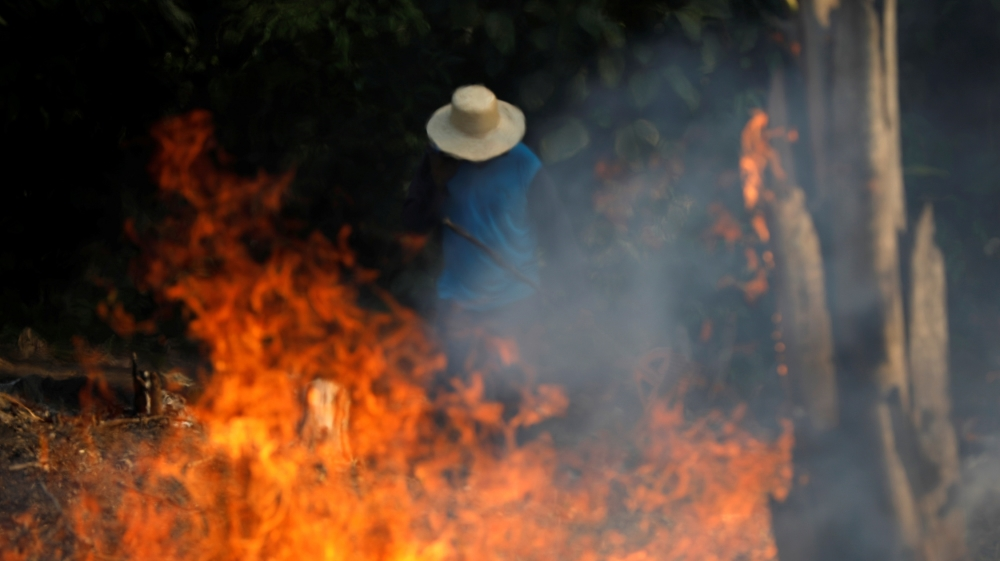 A man works in a burning tract of Amazon jungle as it is being cleared by loggers and farmers in Iranduba, Amazonas state, Brazil August 20, 2019