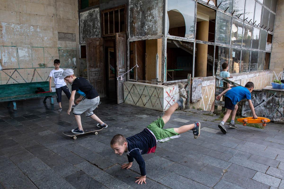 IDP children play outside an abandoned Sanatorium. Skateboarding is a popular pastime. [Taylor Weidman/Al Jazeera]