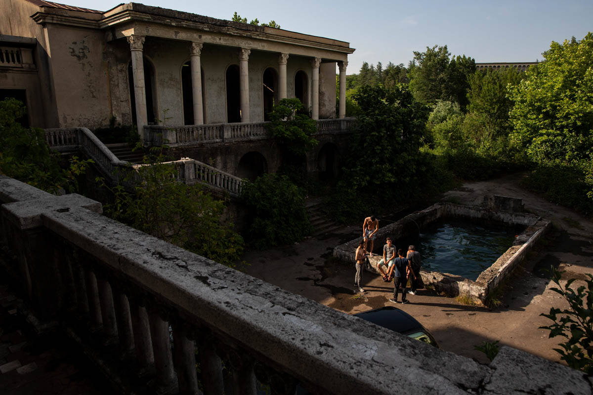 Young men relax by a pool at Sanatorium Medea in Tskatulbo. The pool is popular among residents and young people from various sanatoriums meet here to swim. [Taylor Weidman/Al Jazeera]