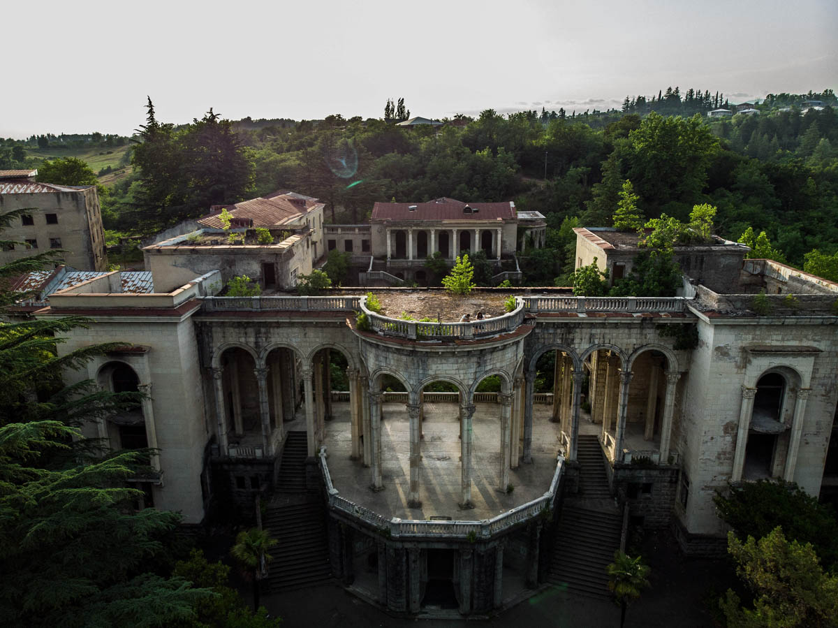 A couple stand atop Sanatorium Medea in Tskatulbo, Georgia. This columned sanatorium remains popular with couples on dates and wedding parties for photoshoots. [Taylor Weidman/Al Jazeera]