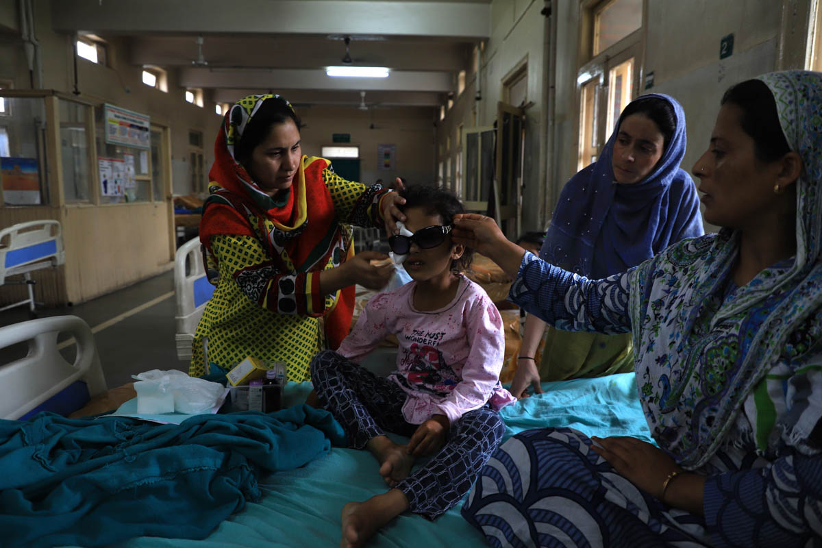 Family members attend Munifa Nazir at Shri Maharaja Hari Singh hospital in Srinagar on August 17. The six-year-old girl from Safakadal was hurt in the right eye after paramilitary forces targeted her with a slingshot on Eid day when she was out with her uncle. A relative attending her said she is unable to see from her right eye. [Syed Shahriyar/Al Jazeera]