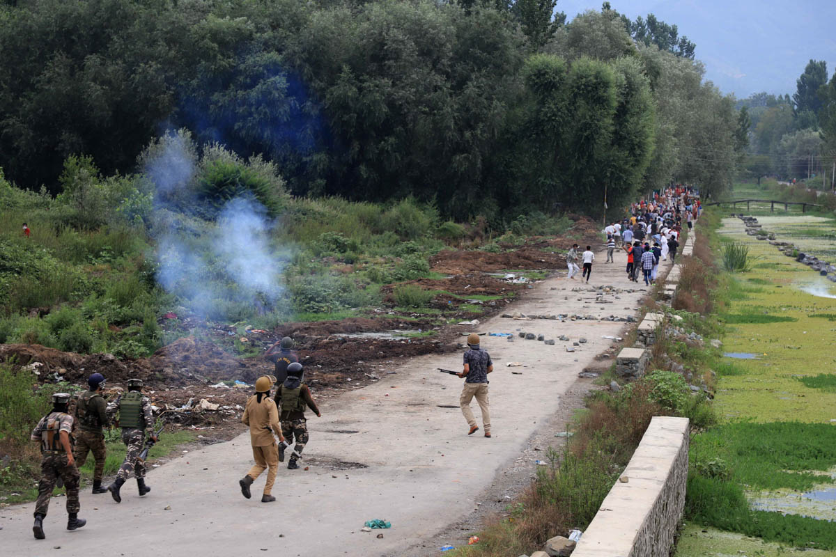 Indian police and paramilitary soldiers fire tear gas and pellets as they chase demonstrators during protests on the outskirts of Srinagar. [Syed Shahriyar/Al Jazeera]