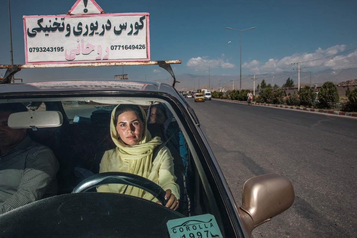 Razia, 24, took additional lessons to become one of the drivers of the Pink Shuttle, billed as 'the first and only service in Afghanistan driven uniquely by female drivers for female passengers'. [Alessio Mamo/Al Jazeera]