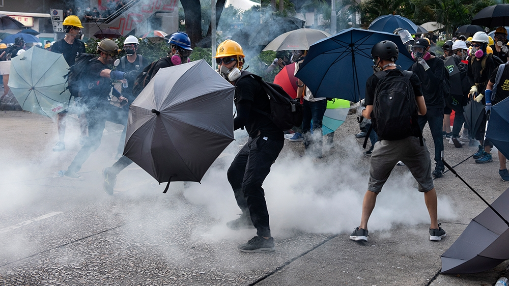 Anti-extradition protesters react after tear gas was fired at them by police during clashes in Wong Tai Shin area in Hong Kong, China, 05 August 2019. Hong Kong is in the midst of a citywide strike fo