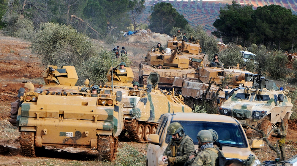In this Jan. 28, 2018, file photo, Turkish troops take control of Bursayah hill, which separates the Kurdish-held enclave of Afrin from the Turkey-controlled town of Azaz, Syria. The violence raging o