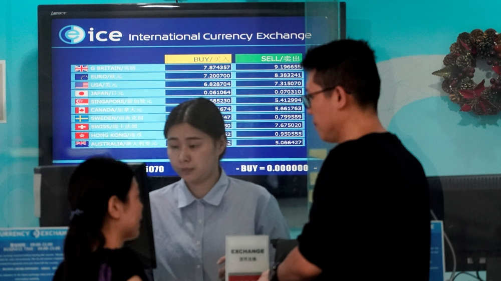 Customers are served at a counter at a currency exchange store in Shanghai