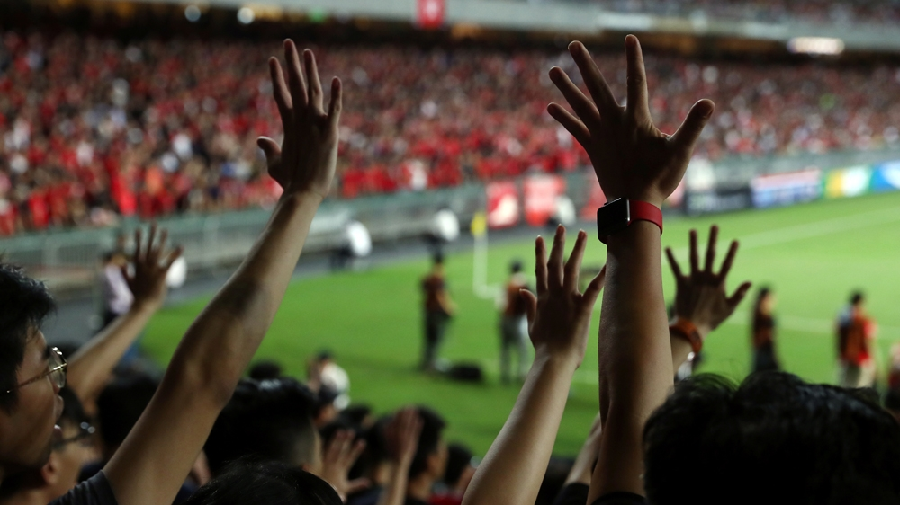 Soccer fans gesture their hands in support of anti-government protesters during a football World Cup qualifier match between Hong Kong and Iran, at Hong Kong Stadium, China September 10, 2019. REUTERS