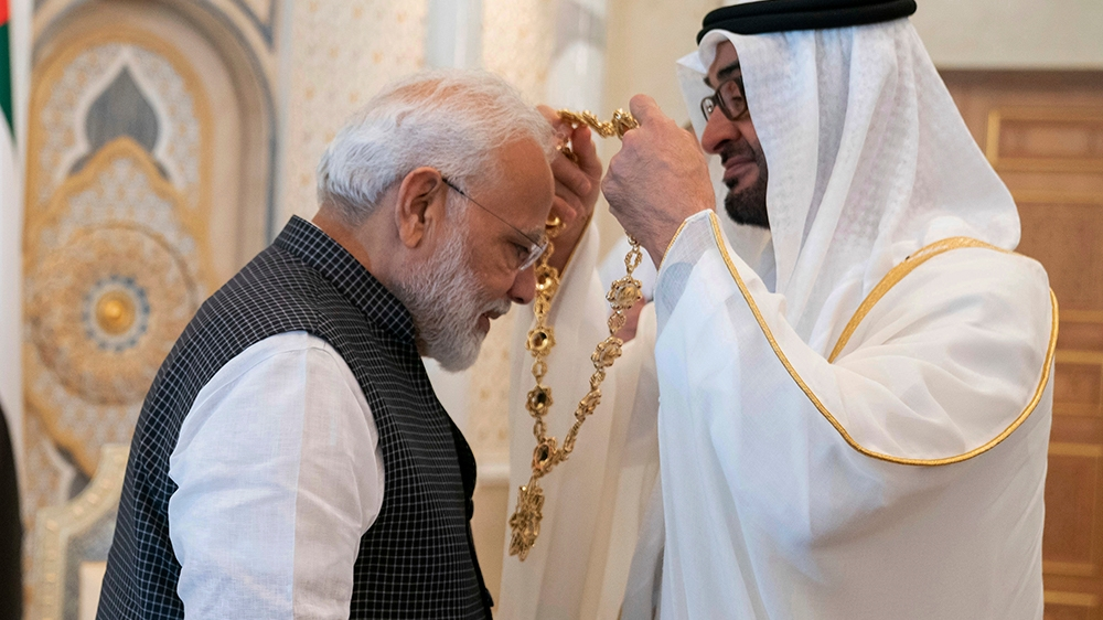 In this photograph made available by the state-run WAM news agency, Indian Prime Minister Narendra Modi, left, receives a medal during his induction to the Order of Zayed from Sheikh Mohammed bin Zaye