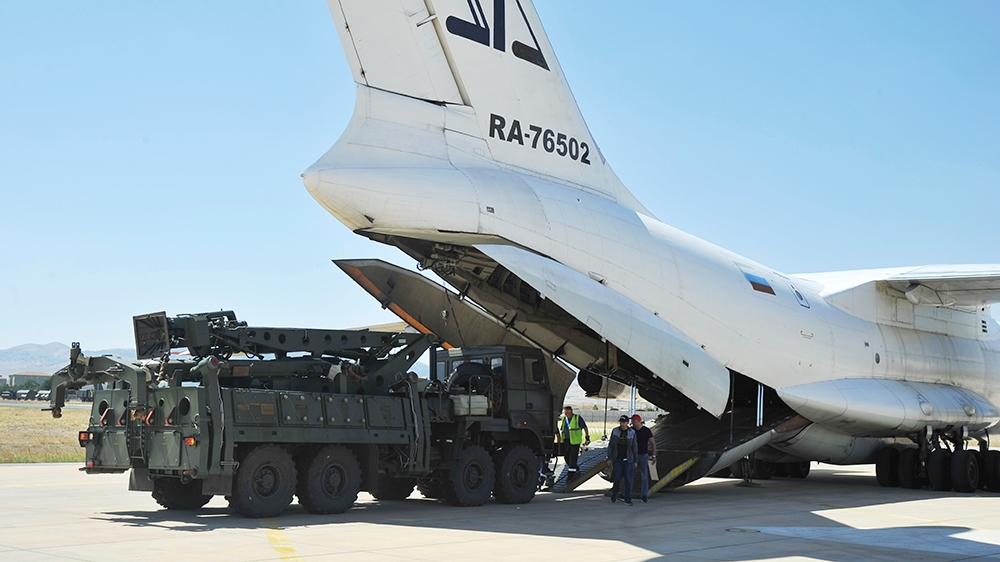 Military officials work around a Russian transport aircraft, carrying parts of the S-400 air defense systems, after it landed at Murted military airport outside Ankara, Turkey, Tuesday, Aug. 27, 2019.