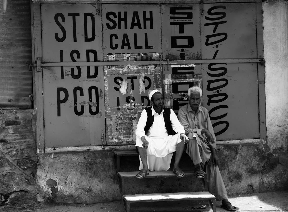 Two Kashmiri men sit outside a shuttered phone-placement shop. Hours before scrapping of Kashmir's special status, the region's seven million inhabitants were put under an unofficial curfew and an indefinite communications blackout. [Sanna Irshad Mattoo/Al Jazeera]