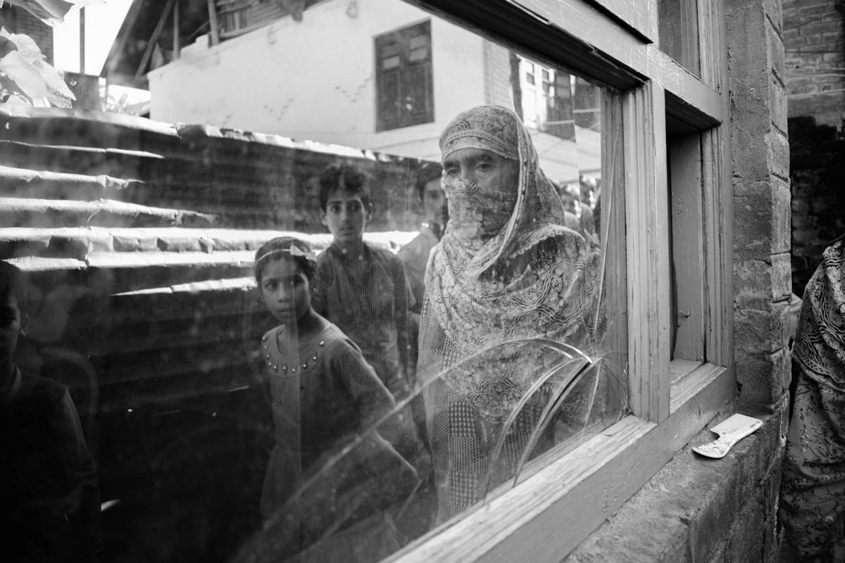 Arif's mother shows the damage to her house caused by the police raid. The Dars and other families wait for any news about their family members. Many young men who were arrested have been taken to jails hundreds of kilometres away from Kashmir. [Sanna Irshad Mattoo/Al Jazeera]