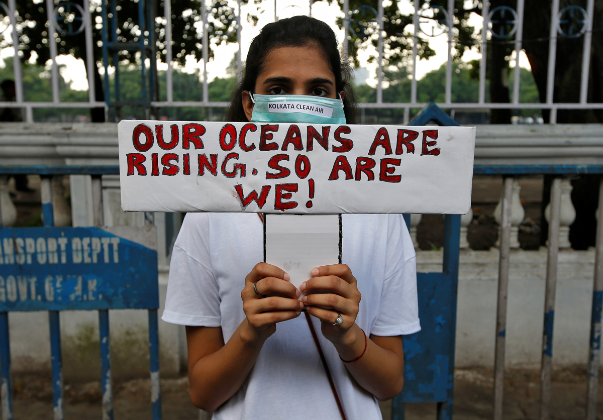 A student wearing a mask holds a placard with a message reading 'Our oceans are rising, so are we!' as she takes part in a Global Climate Strike rally in Kolkata, India. [Rupak /Reuters]
