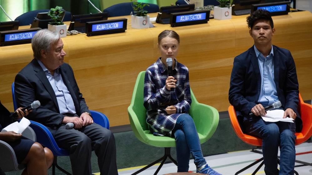 Swedish environmental activist Greta Thunberg, center, speaks to guests next to U.N. Secretary-General Antonio Guterres
