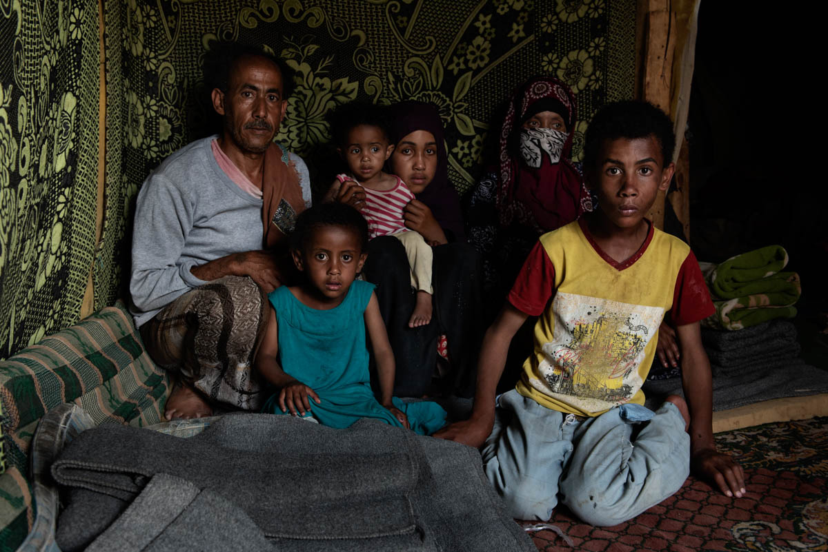 Ali Nasser el-Kahsi with his family inside a tent of the IDP camp in Khamer, Yemen. [Alessio Romenzi/Al Jazeera]