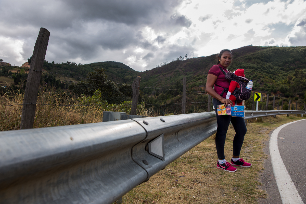 """Marielis Rojas, a 31-year-old migrant, carried her two-month-old baby with sock-mittens and packages of food and juice delivered to them just moments before by a car passing by while she and her family were asking to hitchhike. She cried when they handed it to her. They want to eventually land in one of Colombia's big cities to work, but do not know where. """"Look, we've had to put socks on his little hands because they were so cold,"""" Rojas said. """"We don't know where we're going to spend the night because it's six or seven hours to the next refuge ... I'm scared the baby is going to die in my arms."""" [Megan Janetsky/Al Jazeera]"""