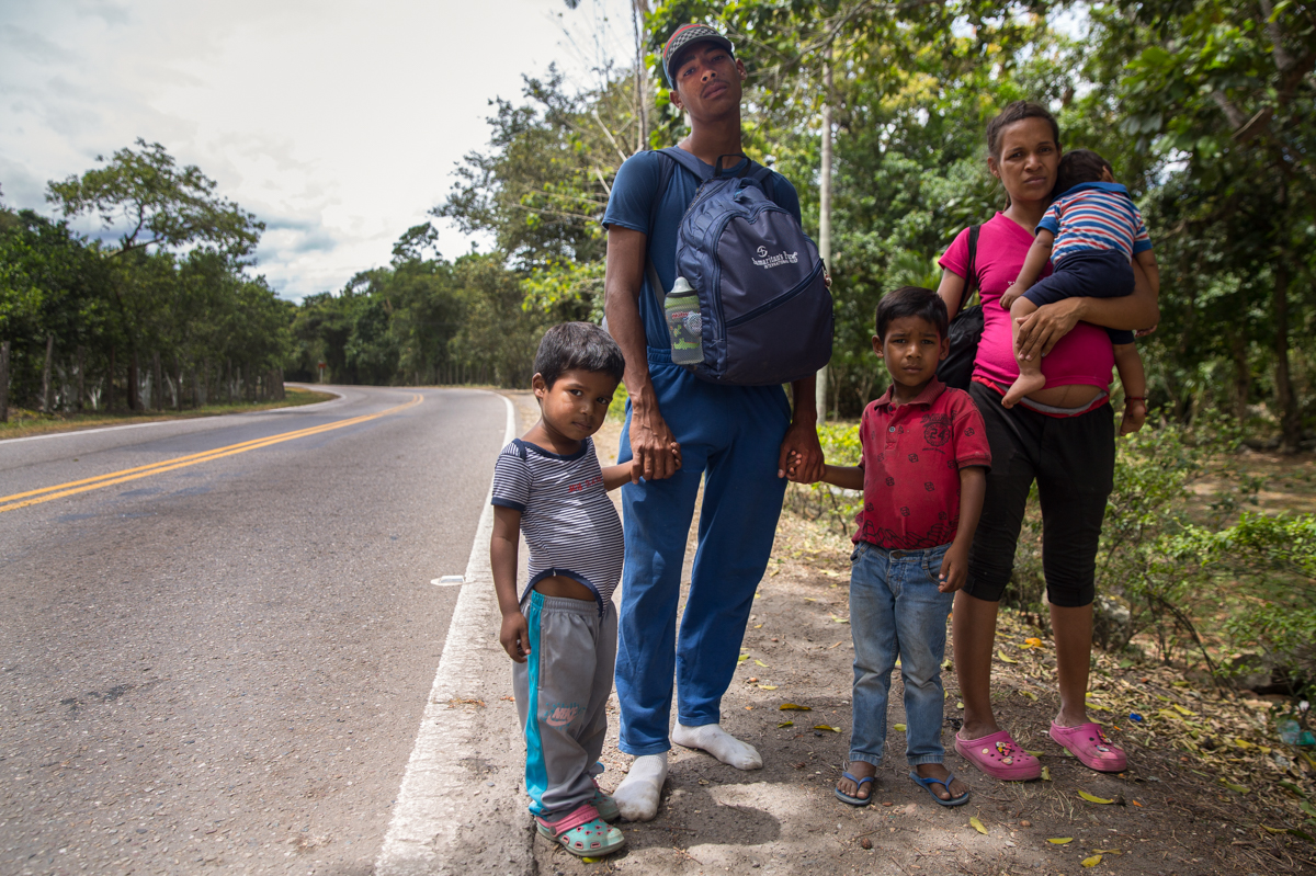 """Dainer Garcia, his seven-month-pregnant wife and three children - aged one, three and four years - left Aragua, Venezuela with no money and were walking to Ecuador, carrying the kids along the way. """"In Venezuela, there isn't anything, there's not enough medicine for her to give birth, there's no help,"""" Garcia said. 'I'm scared that the walk is going to hurt the baby, but we have to keep going."""" [Megan Janetsky/Al Jazeera]"""