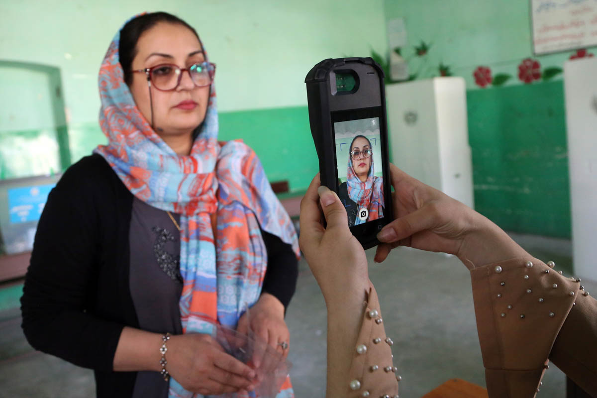 As part of the biometric voting system, an election official takes the picture of a woman before she casts her ballot in Kabul. [Rahmat Gul/AP Photo]