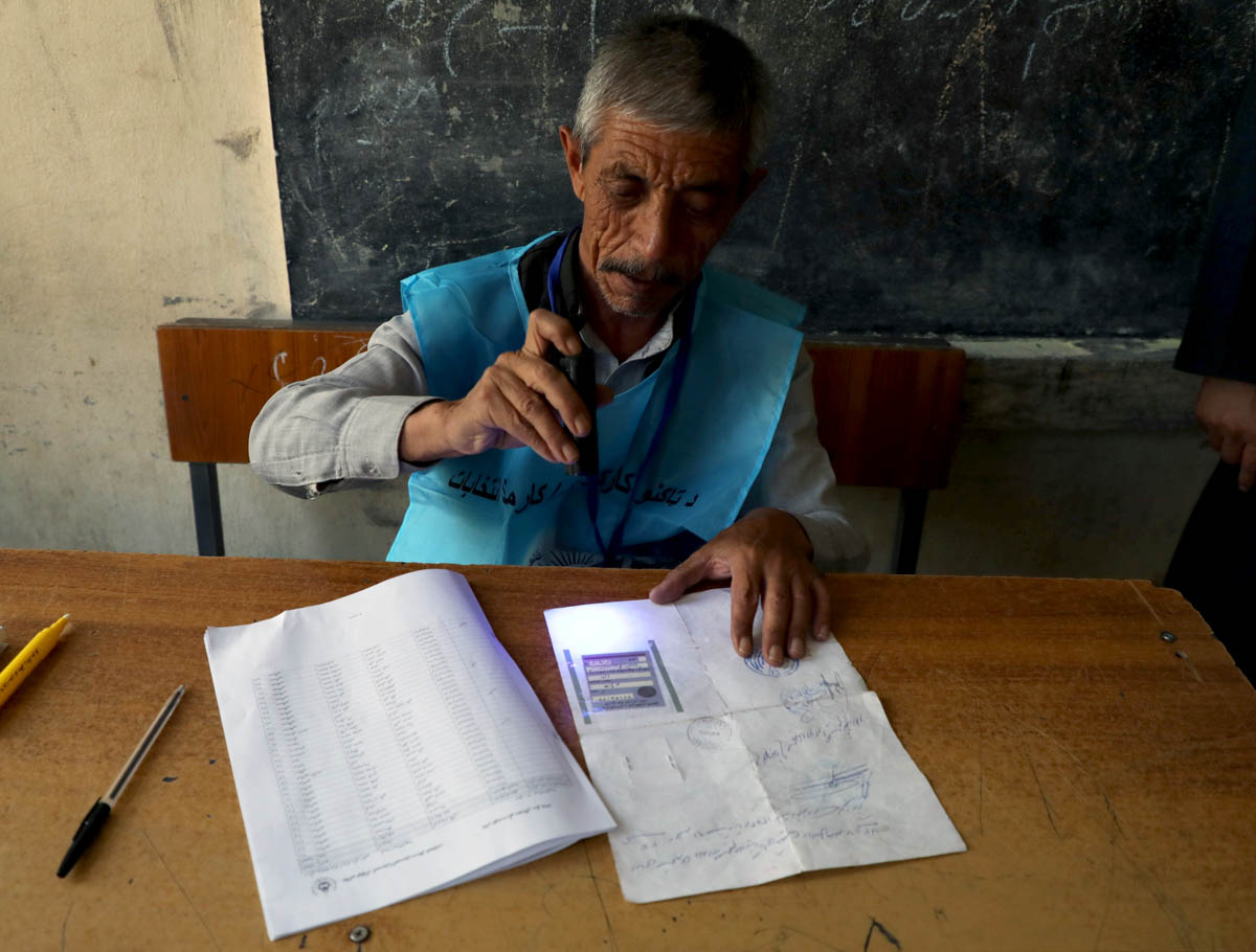 An election official checks a voter's documents with a UV flashlight at a polling station in Kabul. [Omar Sobhani/Reuters]