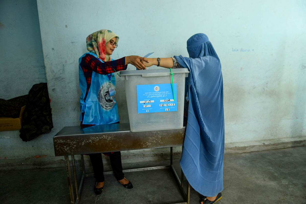 An Independent Election Commission (IEC) official, left, helps a woman cast her vote at a polling station in Herat. [Hoshang Hashimi/AFP]