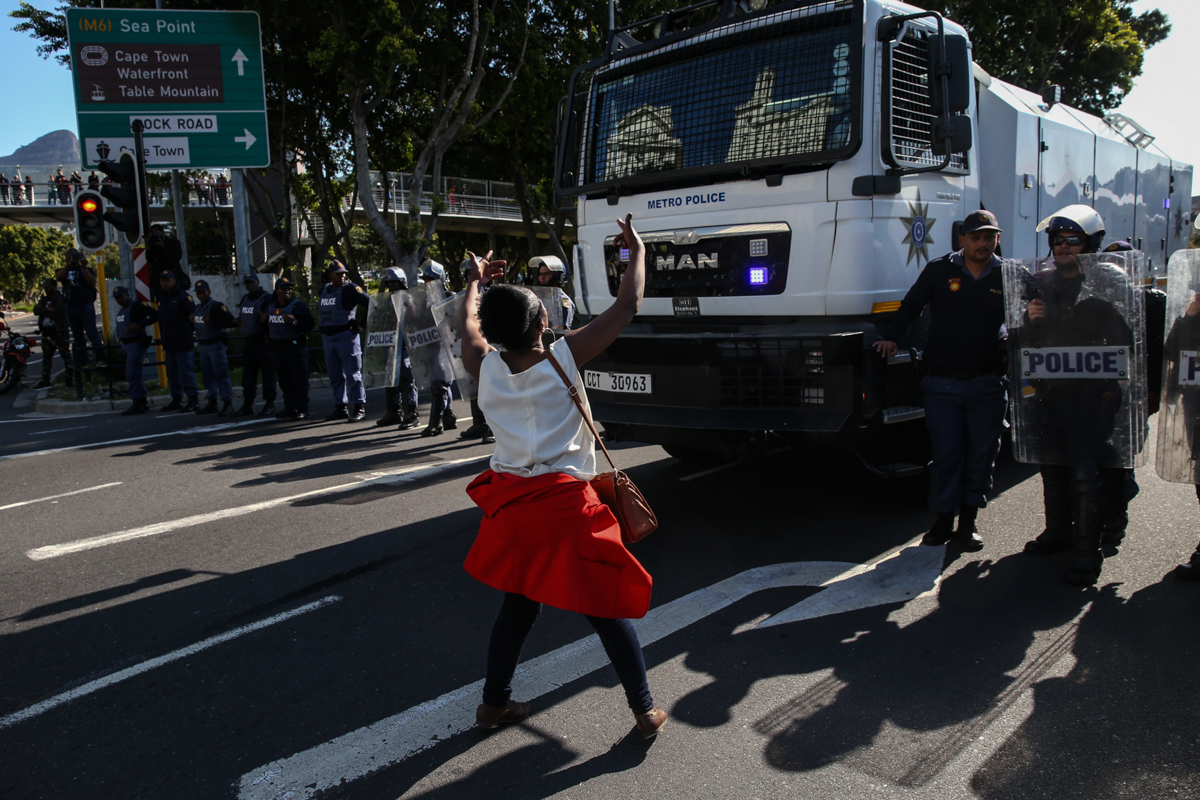 Protesters continue to block streets in different parts of the city near the Cape Town International Convention Centre (CTICC). Through the course of the day, police would again use the water cannon and stun grenades on protesters to disperse them. 'Shoot me,' shouts a protester while waiting in the street. [Ashraf Hendricks/Al Jazeera]