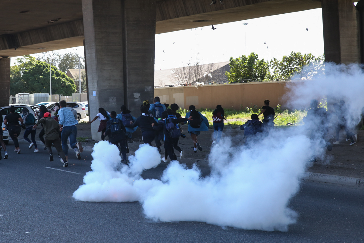 Police use stun grenades to disperse protesters from entering and blocking the highway. 'We're protesting against violence, not for it,' said a distressed student in tears after the stun grenades were fired. 'Where is this when we get f****** raped,' she said, pointing at the police. [Ashraf Hendricks/Al Jazeera]