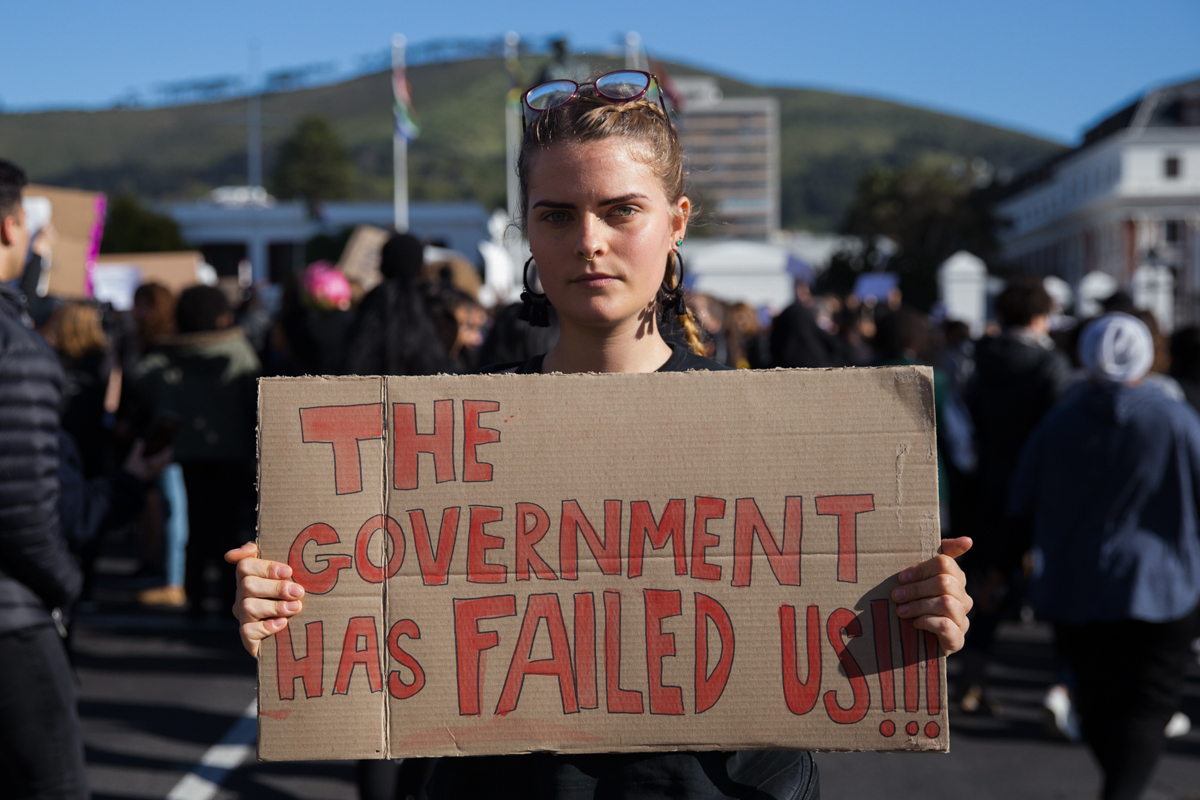 'We are here because enough is enough,' said Emily Shay, a UCT student, standing outside parliament. She said that women are scared to live in this country and that the government is failing them. 'I don't know how many rapes and murders they need to see.' [Ashraf Hendricks/Al Jazeera]