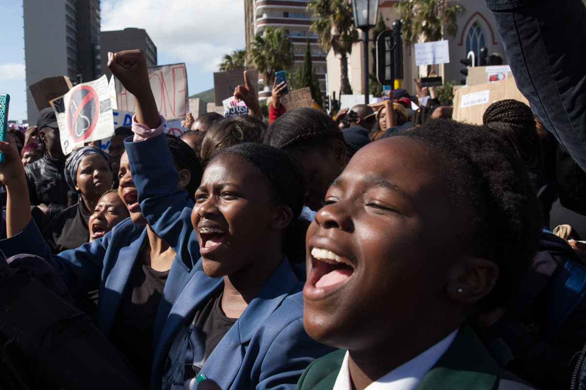 Many high school pupils protest outside the Parliament of South Africa. In the past week alone, South African boxing champion Leighandre Jegels, university student Jesse Hess and 14-year-old Janika Mallo were murdered. [Ashraf Hendricks/Al Jazeera]