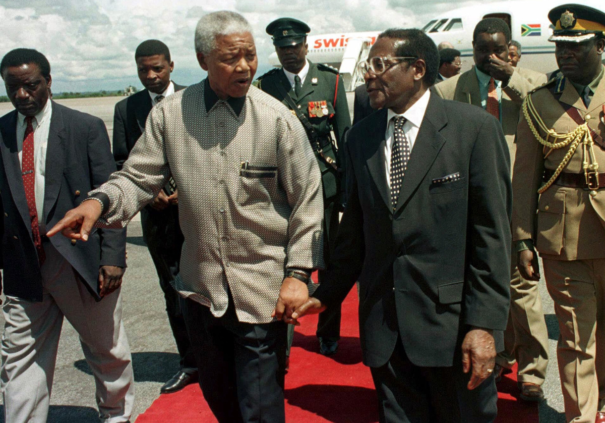 Mugabe and South Africa's former President Nelson Mandela were political leaders and contemporaries whose backgrounds were very similar, however their paths eventually diverged. [Rob Cooper/Reuters]