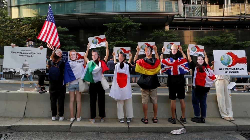 Protesters wear masks of the G7 leaders during a rally to the U.S. Consulate General in Hong Kong