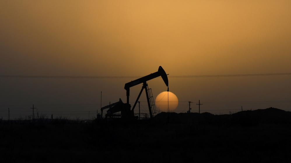 A pump jack operates at sunset in Midland