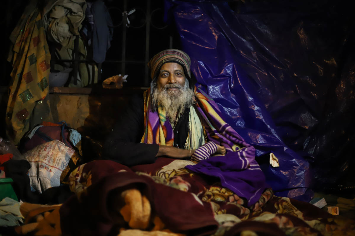 Holding his infant granddaughter in the lap, Mohammad Akram, 71, said he has lived on the footpath for many years with his family of seven. 'Shelter homes are not safe for my daughters as they are filled with drug peddlers and gamblers, who abuse everyone staying there,' said Akram. 'The cold is unbearable and we don't have enough firewood.' [Nasir Kachroo/Al Jazeera]