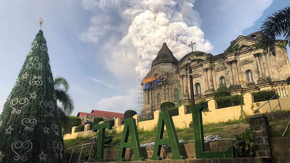 This handout photo taken and received on January 12, 2020 courtesy of Renz Lejarso Guevara shows ash from the Taal volcano (not pictured) in the air, as seen against a church in the foreground in the