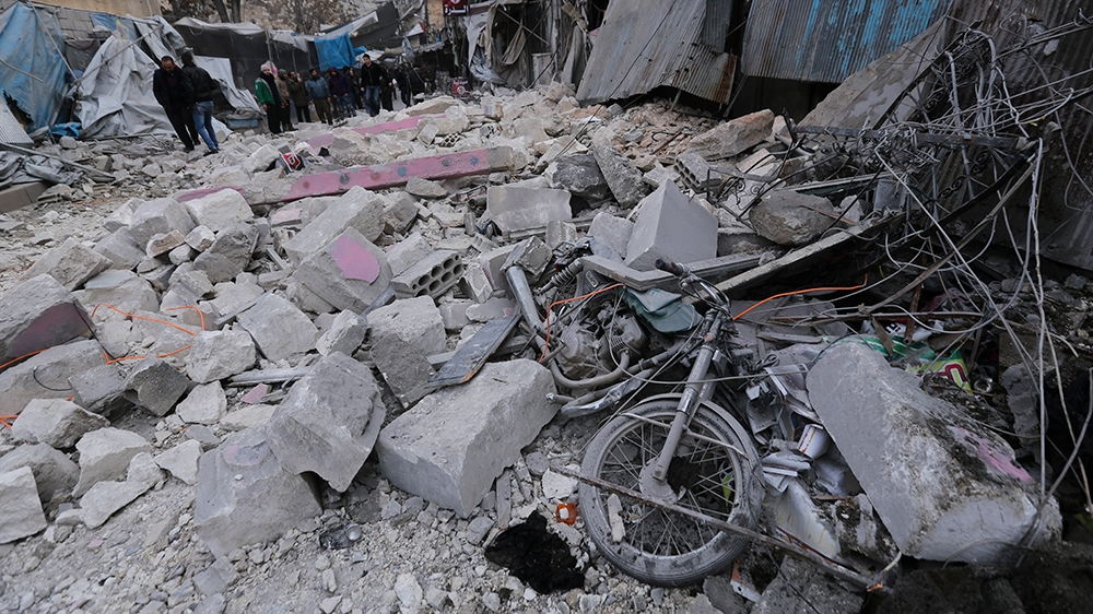 People look at destruction by the government airstrikes in the town of Ariha, in Idlib province, Syria, Wednesday, Jan. 15, 2020. Syrian government warplanes struck a market and an industrial area Wed