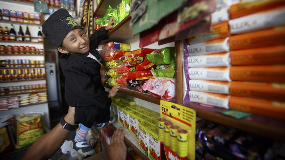 World shortest living man, Magar, tries to take a packet of noodles at a local grocery shop near his home in Pokhara
