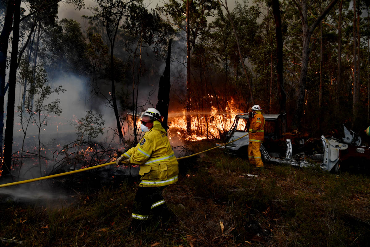 Firefighters from the Rural Fire Service (RFS) conduct property protection near the town of Sussex Inlet in Sydney. Several dangerous bushfires are burning at an emergency level across NSW as weather conditions deteriorate with temperatures expected to rise in the face of a gusty southerly change. [Sam Mooy/Getty Images]