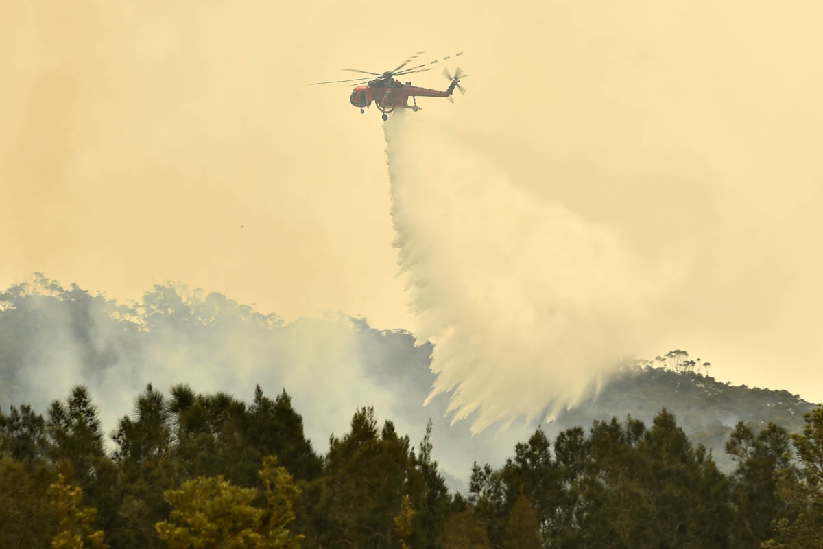A helicopter drops water on a bushfire outside of Batemans Bay in New South Wales. [Peter Parks/AFP]