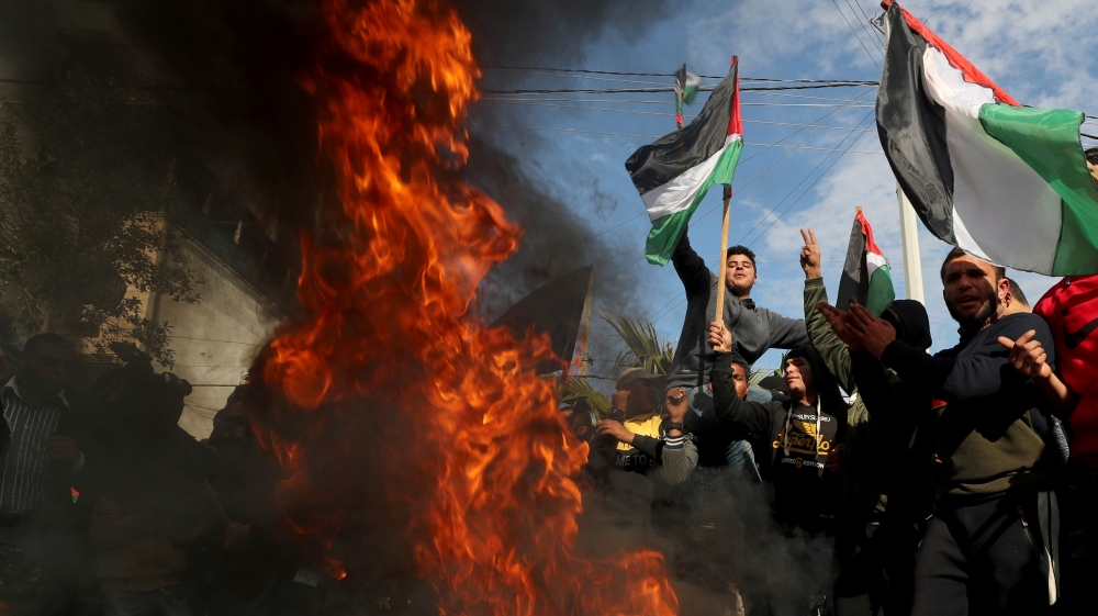 Palestinians protest as tires burn ahead of the announcement by U.S. President Donald Trump of his long-delayed Mideast peace plan, in Gaza City