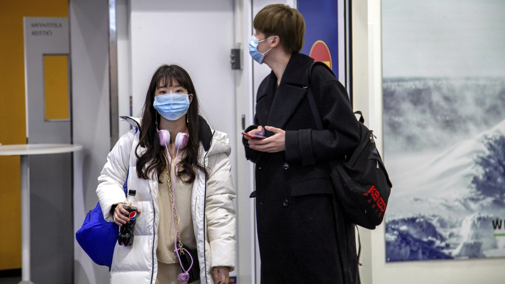 Air travellers wear masks as they arrive at Ivalo Airport, Finland January 24, 2020. On Thursday, two tourists visiting Finland from Wuhan, China went to a health centre in Ivalo, seeking treatment fo