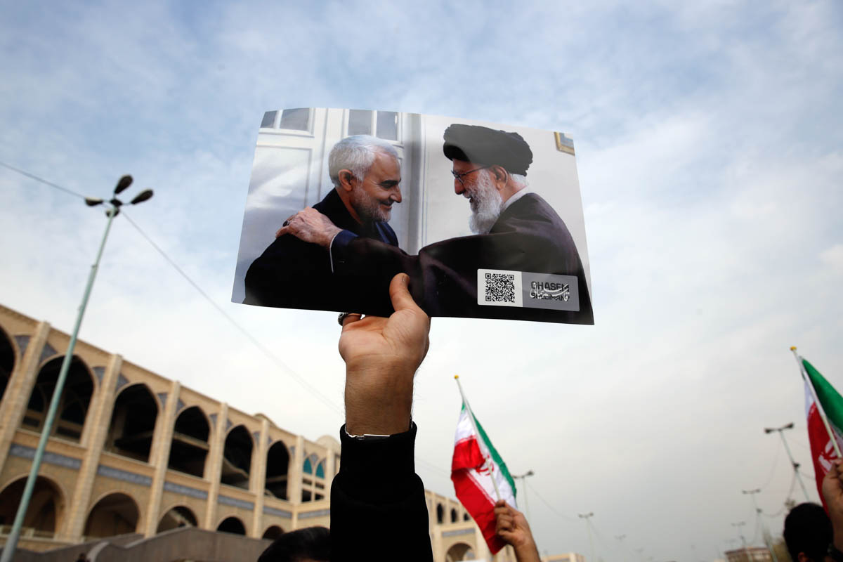 epa08099933 A person as holds a picture showing Iranian Supreme Leader Ayatollah Ali Khamenei (R) greeting Iranian Revolutionary Guards Corps (IRGC) Lieutenant general and commander of the Quds Force