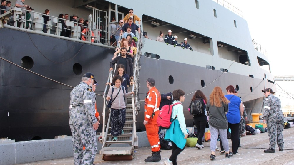 This handout photo taken on January 4, 2020 and received from the Australian Department of Defence shows evacuees (C) disembarking from MV Sycamore at Bluescope Wharf in Hastings, Victoria state. Up t