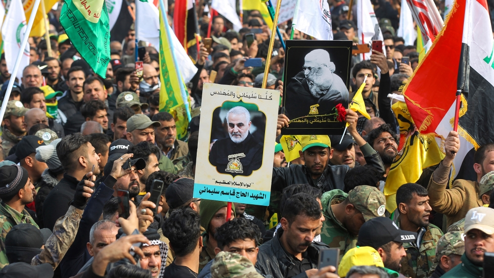 Supporters of the Hashed al-Shaabi paramilitary force and Iraq's Hezbollah brigades attend the funeral of Iranian military commander Qasem Soleimani (portrait) and Iraqi paramilitary chief Abu Mahdi a