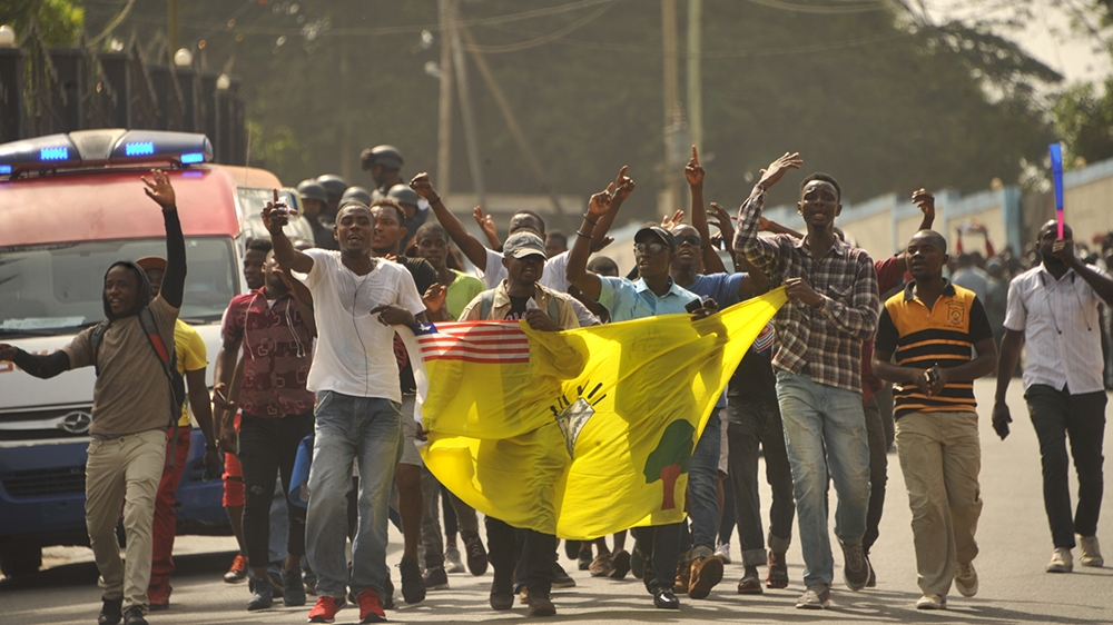 Members of the Council of Patriots (COP)  hold a flag as they protest outside Monrovia's Capitol building against the deepening economic crisis under Liberian President George Weah, in Monrovia on Jan