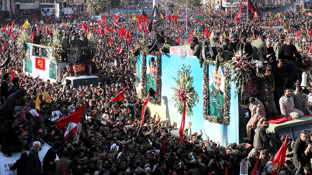 Coffins of Gen. Qassem Soleimani and others who were killed in Iraq by a U.S. drone strike, are carried on a truck surrounded by mourners during a funeral procession, in the city of Kerman, Iran, Tues
