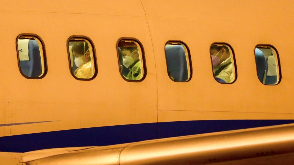 Passengers wearing face masks are seen on a Xiamen Airlines airplane before getting off the charter flight sent by the Chinese government to bring home Hubei residents from Thailand's Bangkok, at Wuha