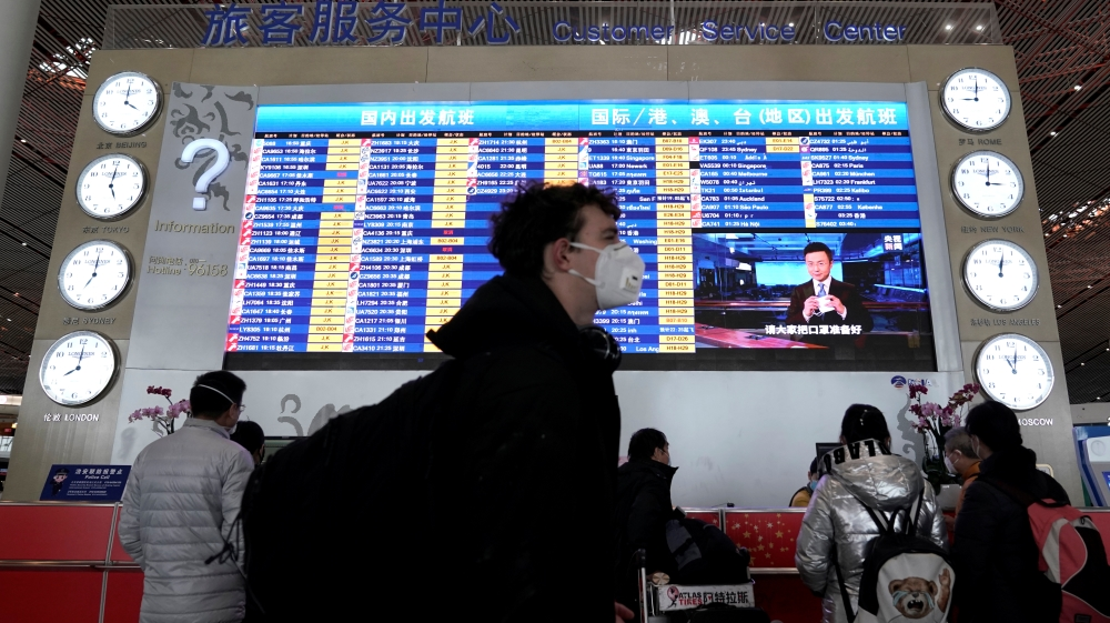A foreign traveller wearing a mask walks past a departures information board at Beijing International Airport in Beijing